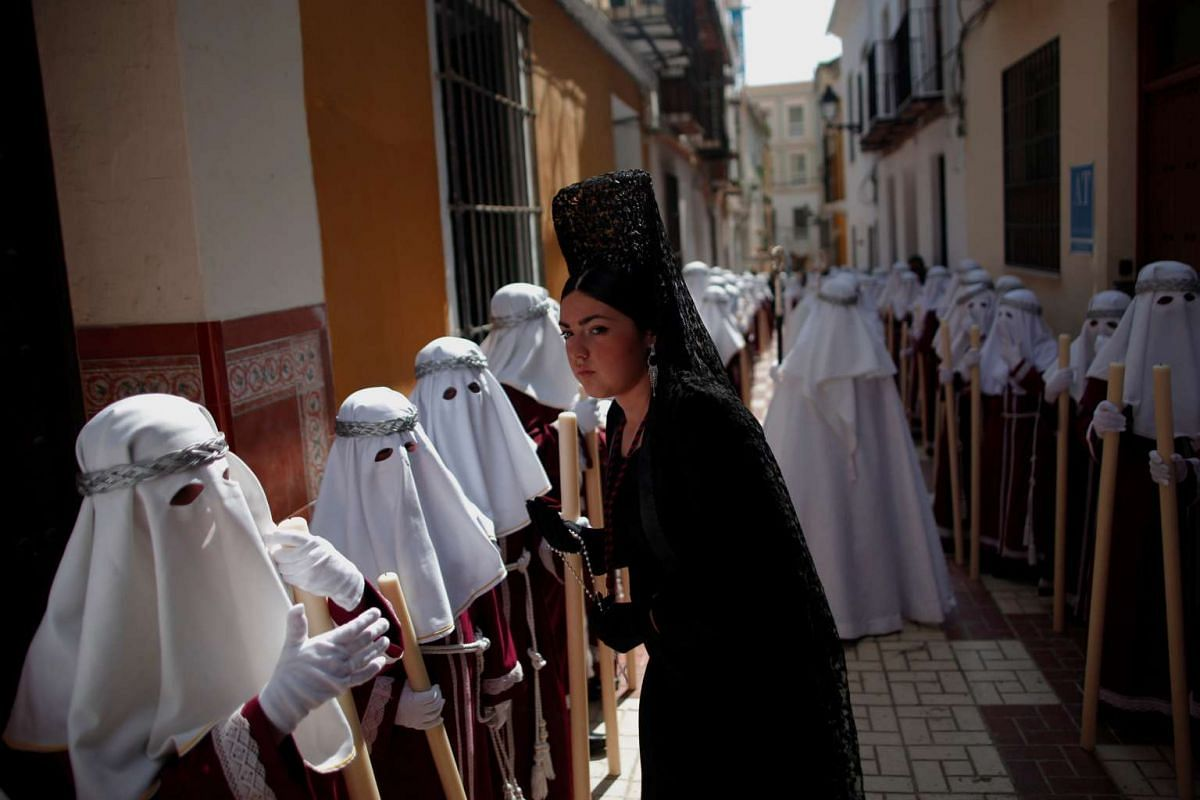 A woman wearing a traditional mantilla dress and penitents take part in the procession of the Gitanos brotherhood during Holy Week in Malaga, southern Spain, on April 10, 2017.