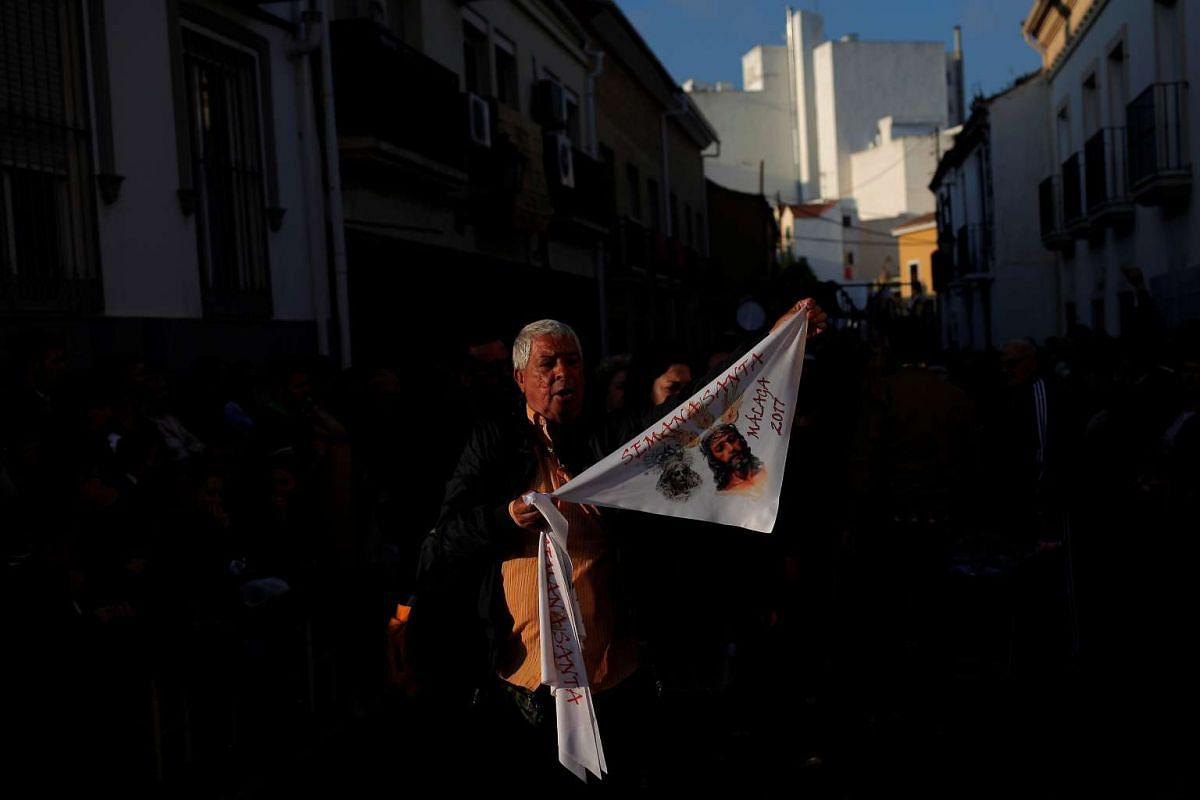 A street vendor displays a souvenir handkerchief of the Virgin and the Christ during the procession of the Cautivo brotherhood during Holy Week in Malaga, southern Spain, on April 10, 2017.