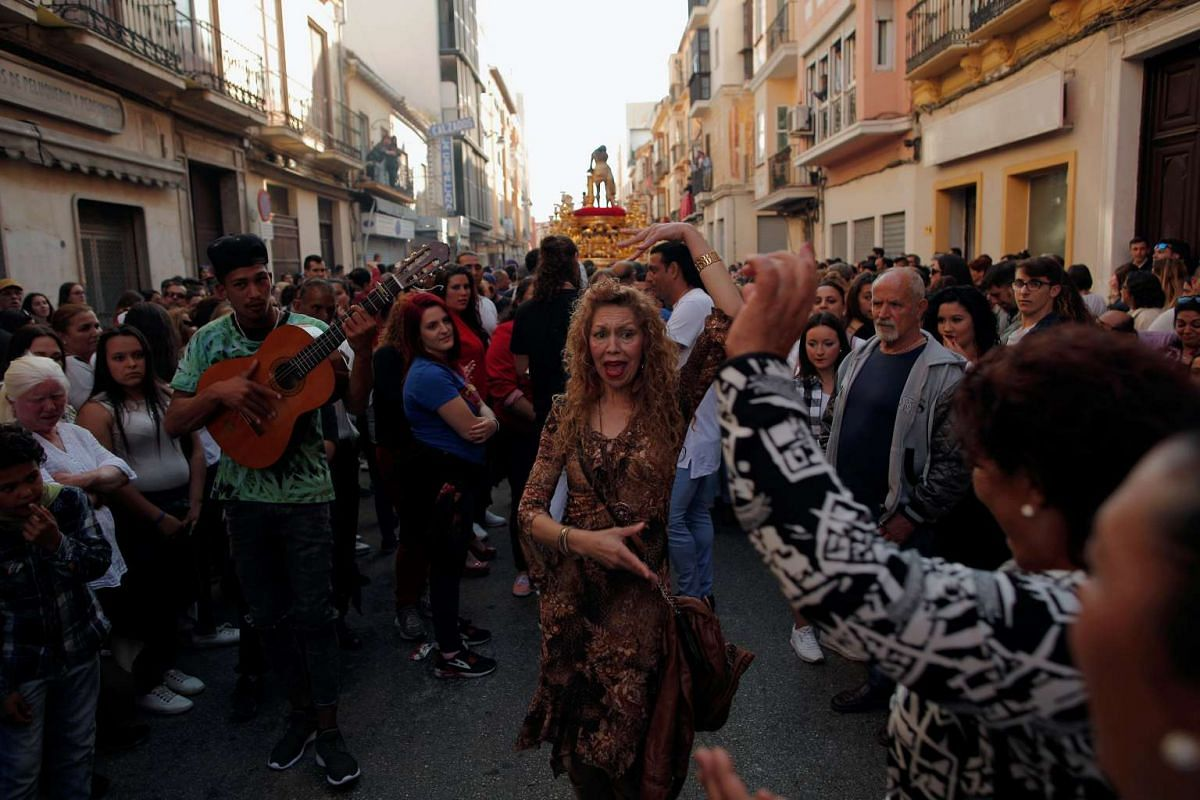 Roma people sing and dance as they take part in a procession of the Gitanos brotherhood during Holy Week in Malaga, southern Spain, on April 10, 2017.