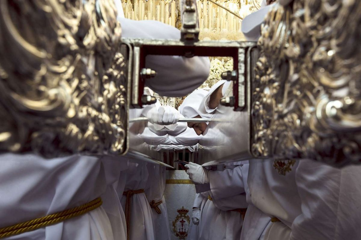 A penitent of the Rocio brotherhood checks his mobile phone prior to a procession on Holy Tuesday in Malaga, Andalusia, southern Spain,  on April 11, 2017.