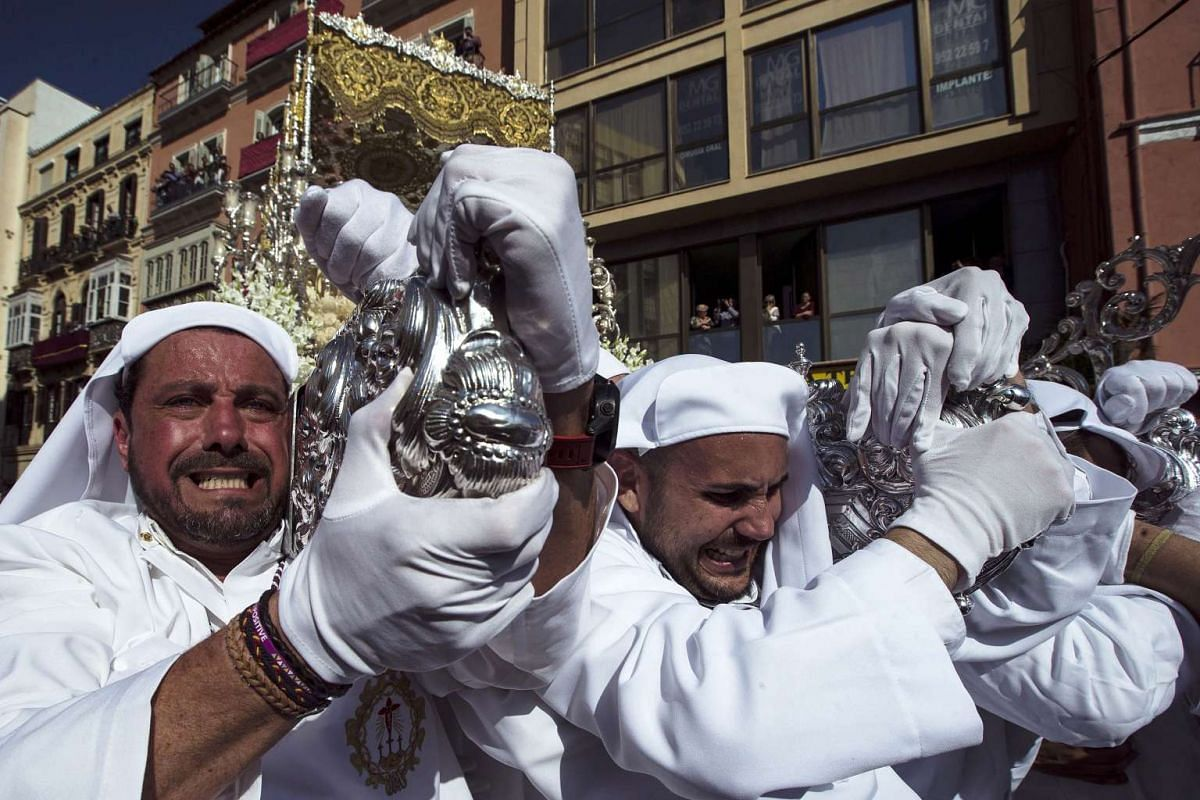 Penitents of the Rocio brotherhood take part in the of the processions of the Holy Tuesday in Malaga, Andalusia, Spain, on April 11, 2017.