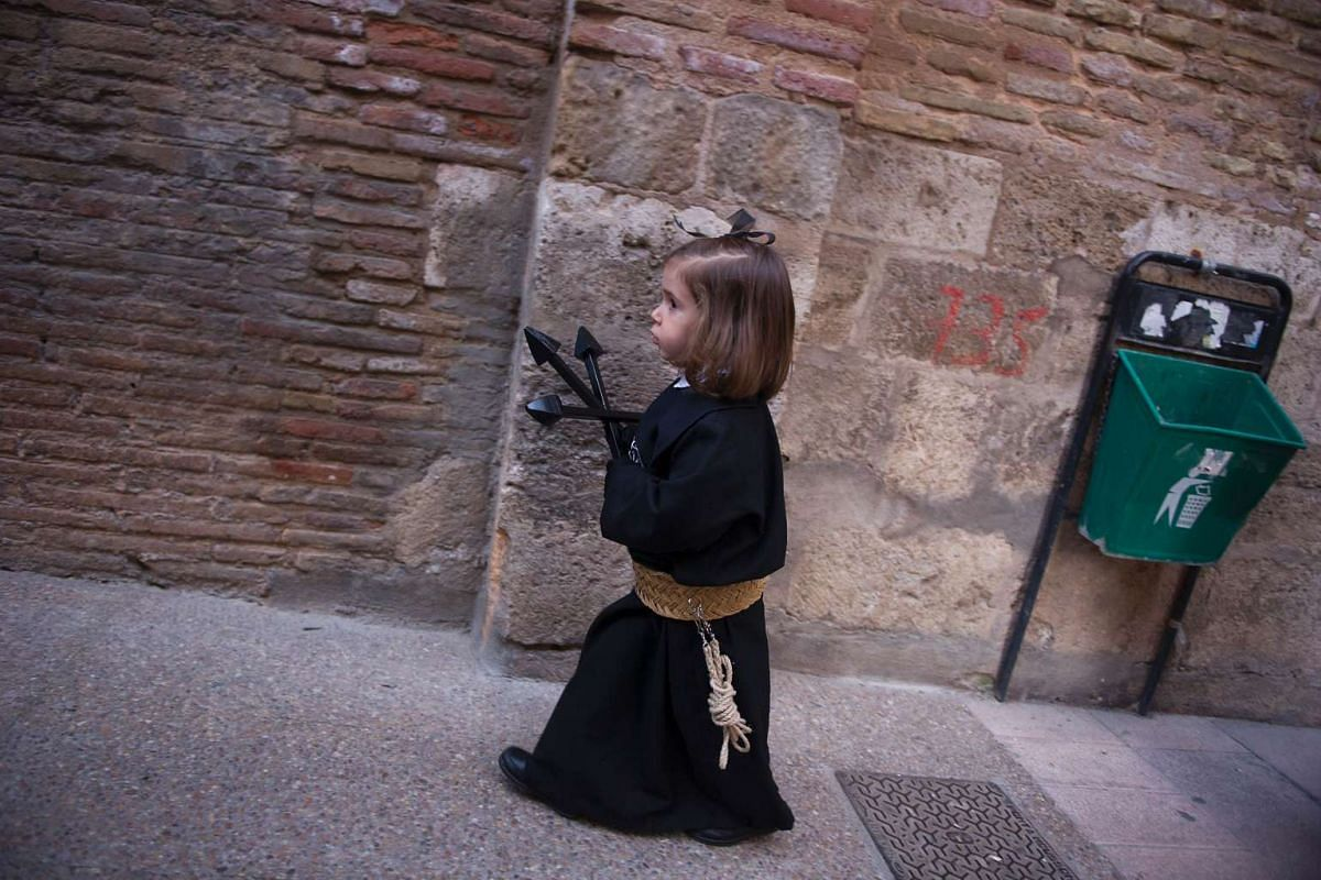 A child penitent of the Silencio del Santisimo Cristo del Rebate brotherhood takes part during a Holy Week procession in the Spanish village of Tarazona on April 11, 2017.