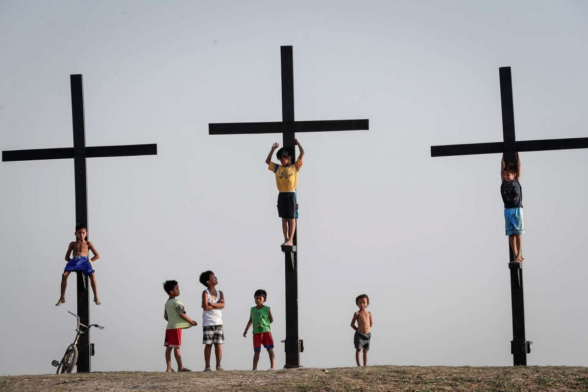 Filipino children play along the site of the re-enactment of the crucifixion of Jesus Christ on Holy Wednesday, San Pedro Cutud village, San Fernando city, north of Manila, Philippines, April 12, 2017. PHOTO: EPA