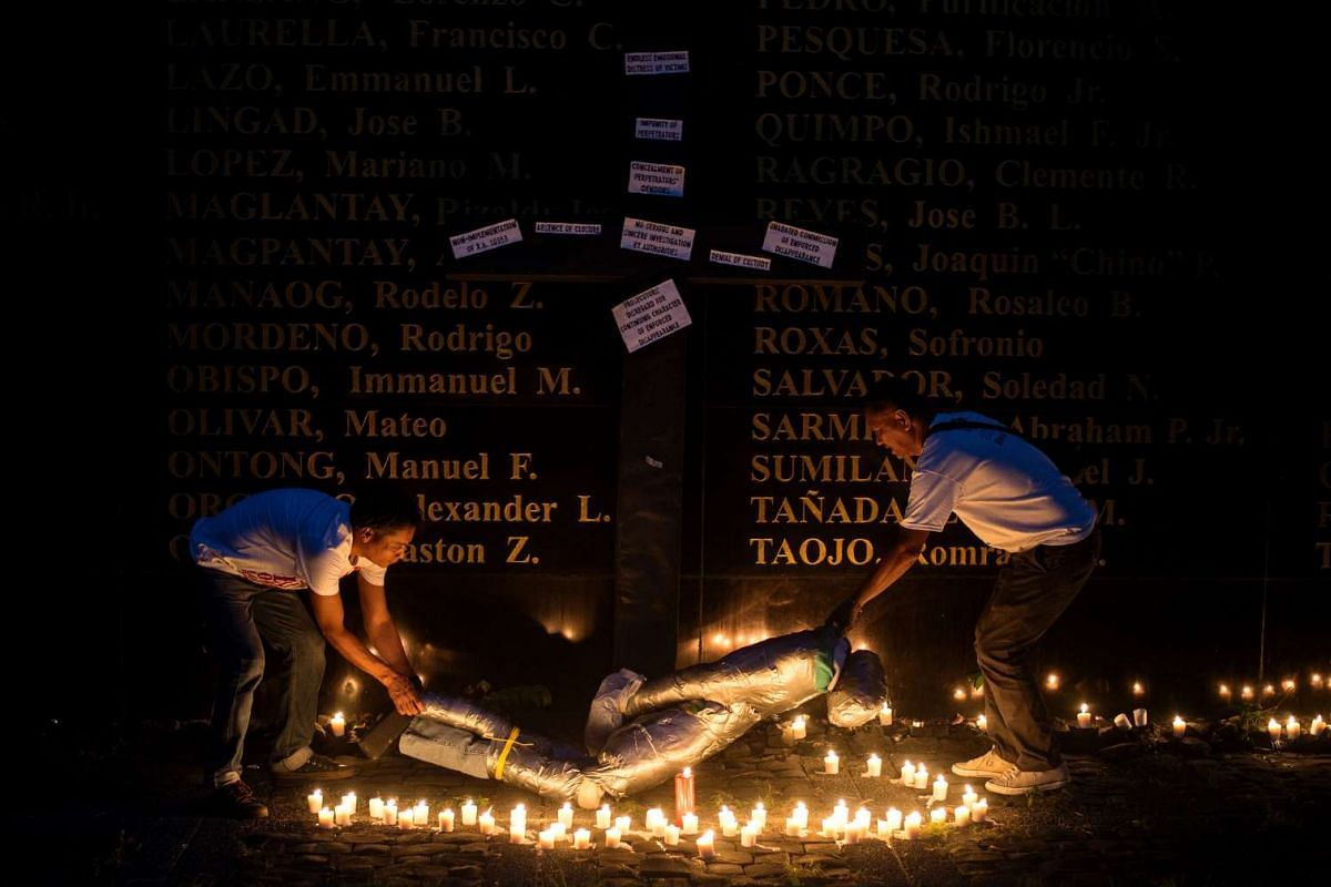 People lift a mock victim during a prayer vigil in support of the families of victims of extra-judicial killings in Manila on April 12, 2017. PHOTO: AFP