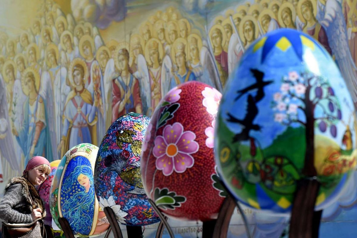 A woman looks at huge Easter eggs as they walk in the open air festival in the center of Kiev on April 12, 2017. PHOTO: AFP