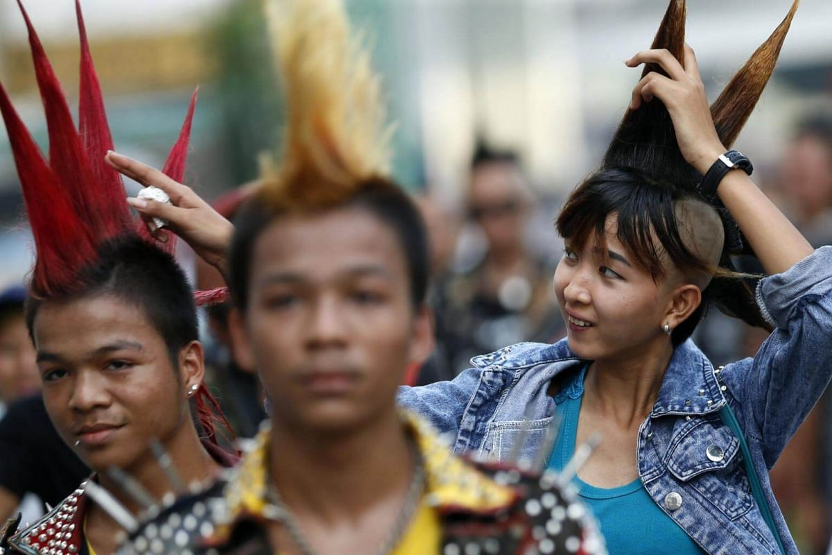 A girl adjusts her mohawk as she and her friends head towards the gathering.
