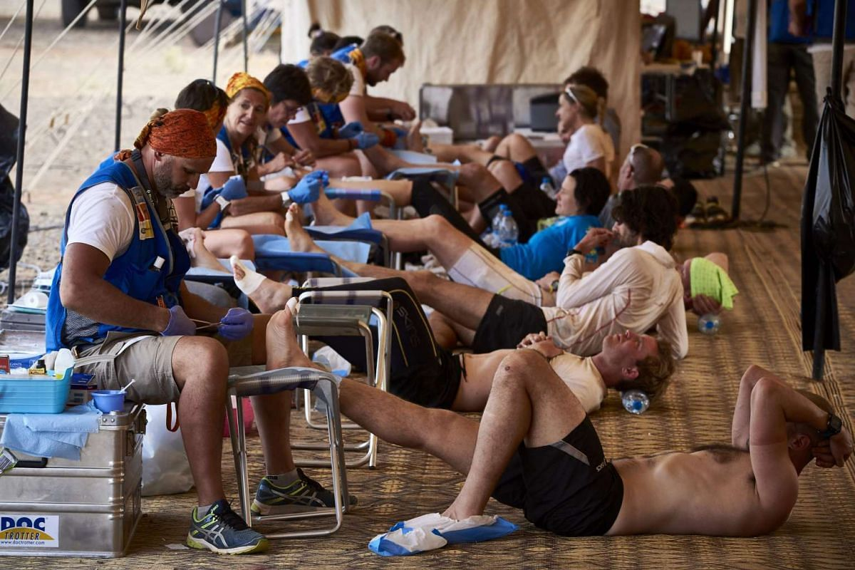 Competitors receive treatment for their tired and aching feet after the Stage 3 of the 32nd edition of the Marathon des Sables between Rich Mbirika and Nord El Maharch in the southern Moroccan Sahara desert on April 11, 2017.