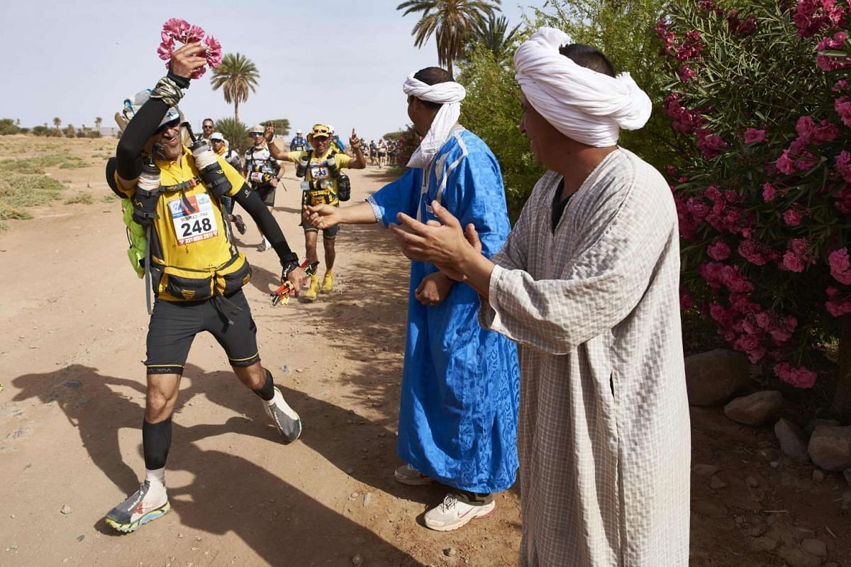 Residents hand flowers to competitors taking part in the 4th Stage of the 32nd edition of the Marathon des Sables between Nord El Maharch and Jebel El Mraier in the southern Moroccan Sahara desert on April 12, 2017.