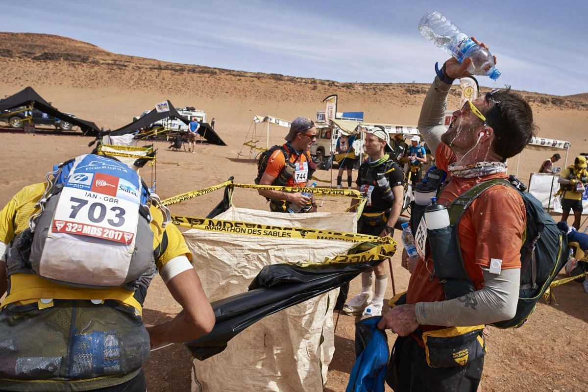 Competitors refresh themselves during the 4th Stage of the 32nd edition of the Marathon des Sables between Nord El Maharch and Jebel El Mraier in the southern Moroccan Sahara desert on April 12, 2017.
