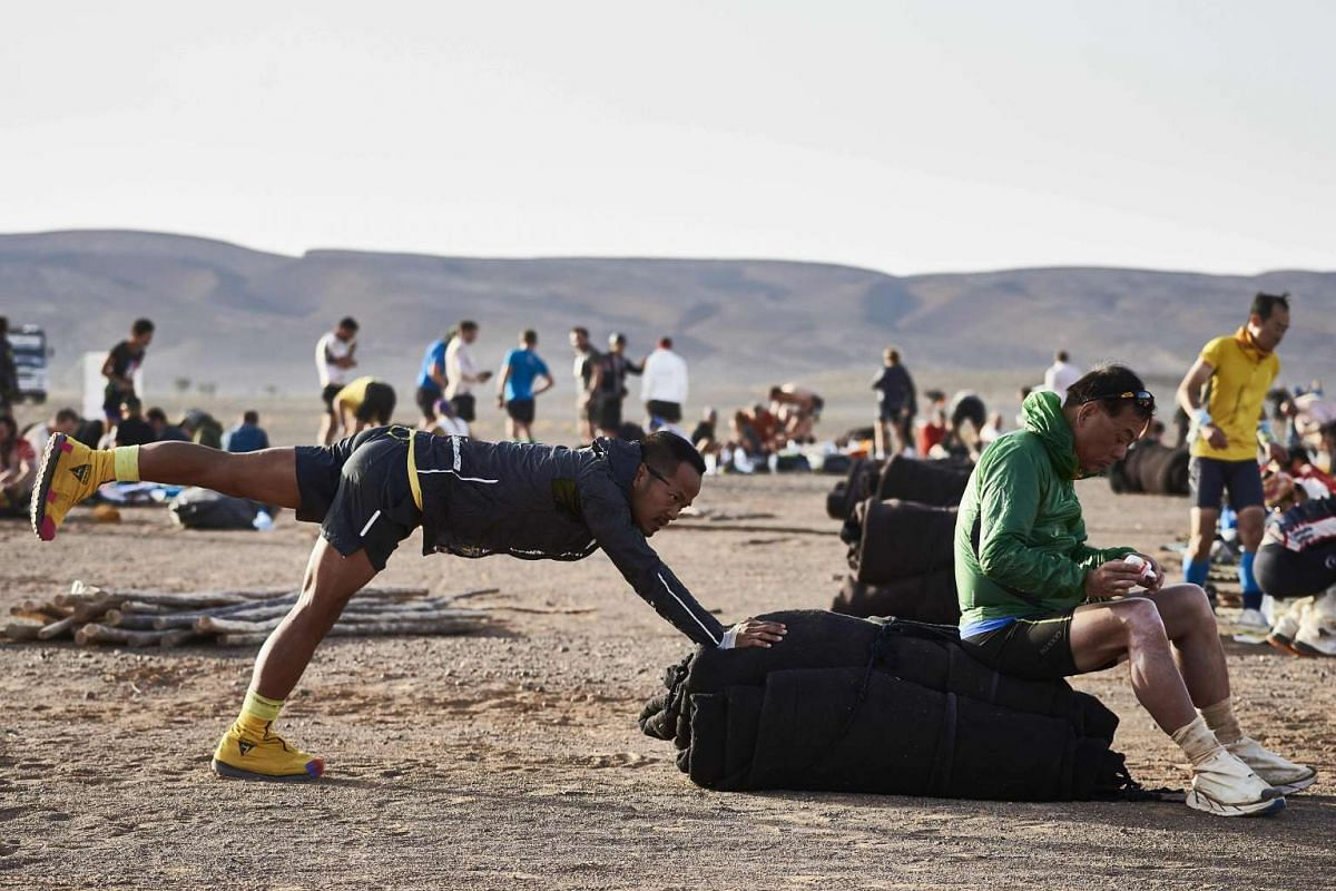 A competitor stretches prior to taking the start of the 4th Stage of the 32nd edition of the Marathon des Sables between Nord El Maharch and Jebel El Mraier in the southern Moroccan Sahara desert on April 12, 2017.