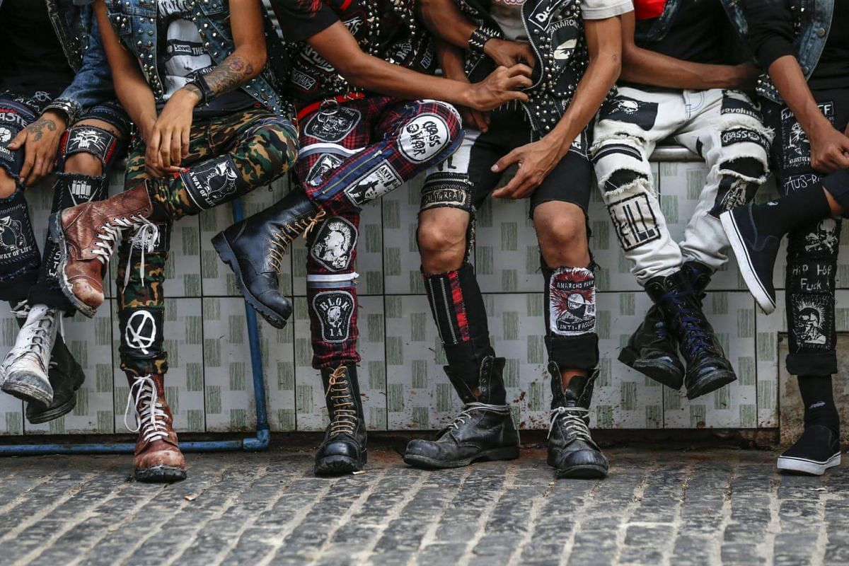 The punks wear customised attire comprising studded jackets and boots with patches sewn on them.
