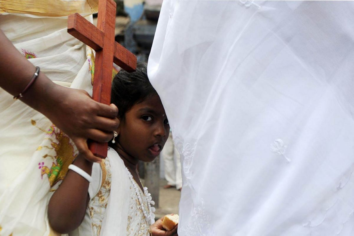 A girls holds a cross as she takes part in a Good Friday procession in Chennai, India.