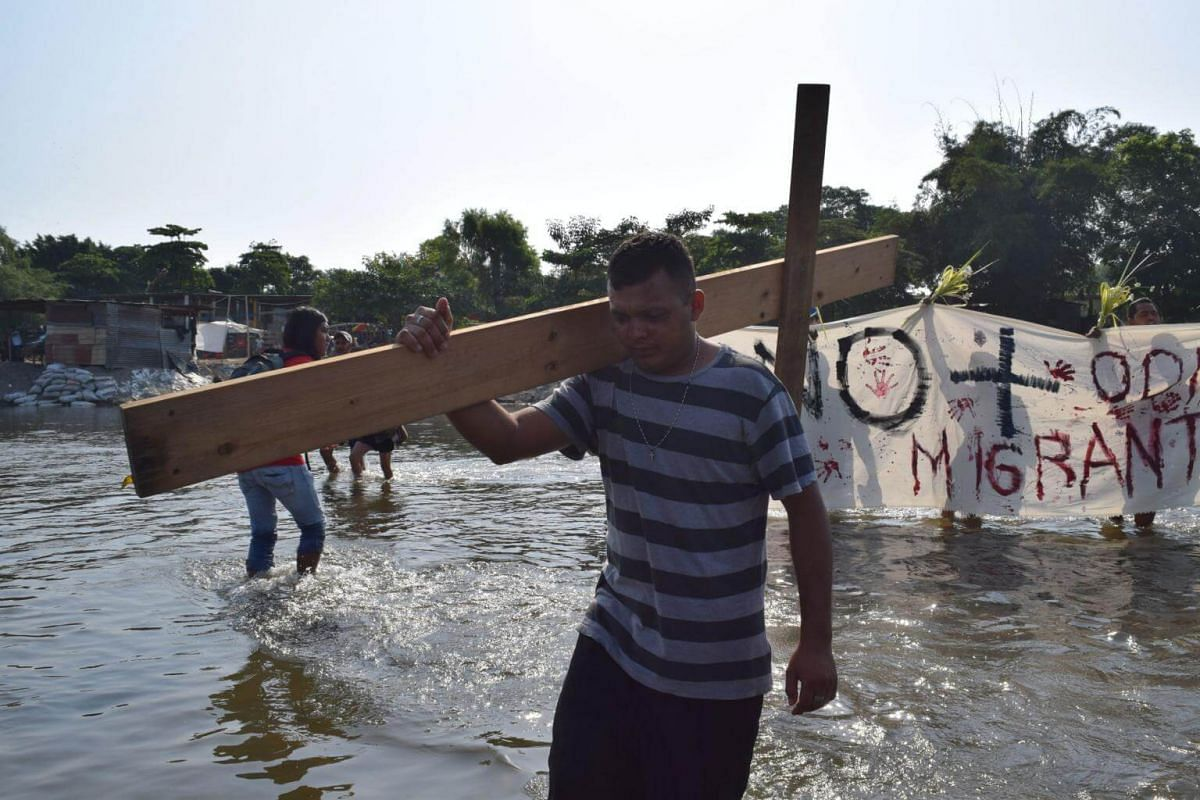 Immigrants cross the Suchiate river, which marks the border between Mexico and Guatemala, to participate in the 'Via Crucis' (Way of the Cross) event on Good Friday in Tapachula, Mexico.