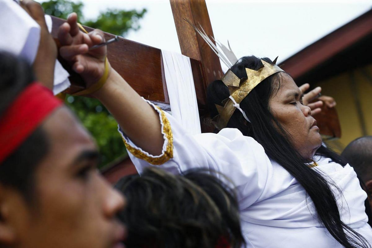 Filipino female penitent Precy Valencia is nailed to a wooden cross for the thirteenth year as spectators watch in the Paombong district of Malolos in the Philippines.