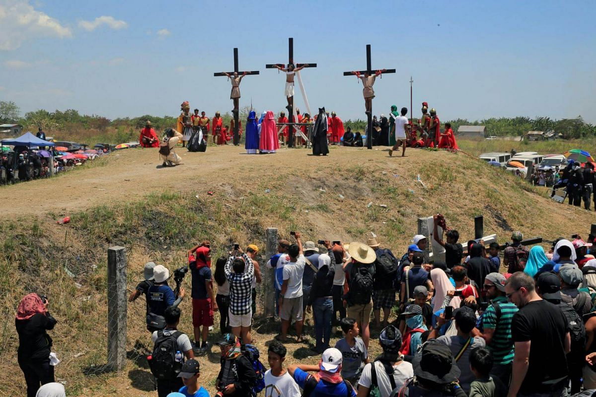 Filipino penitents are seen nailed to wooden crosses during a Good Friday crucifixion re-enactment in San Juan village in the Philippines.