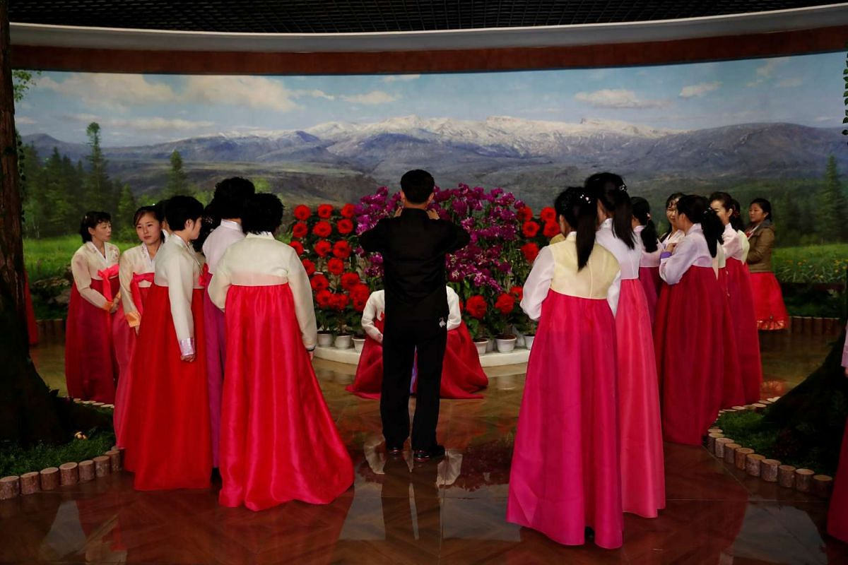 North Koreans attend the opening of new cultural exhibition of celebrations marking founding father Kim Il Sung's 105th birthday in Dandong, Liaoning province, China, on April 15, 2017.