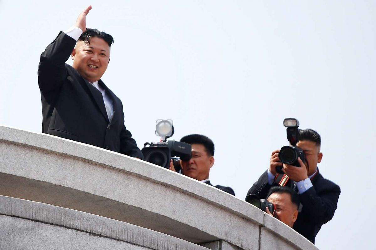 North Korean leader Kim Jong Un waves to people attending a military parade marking the 105th birth anniversary of country's founding father in Pyongyang.