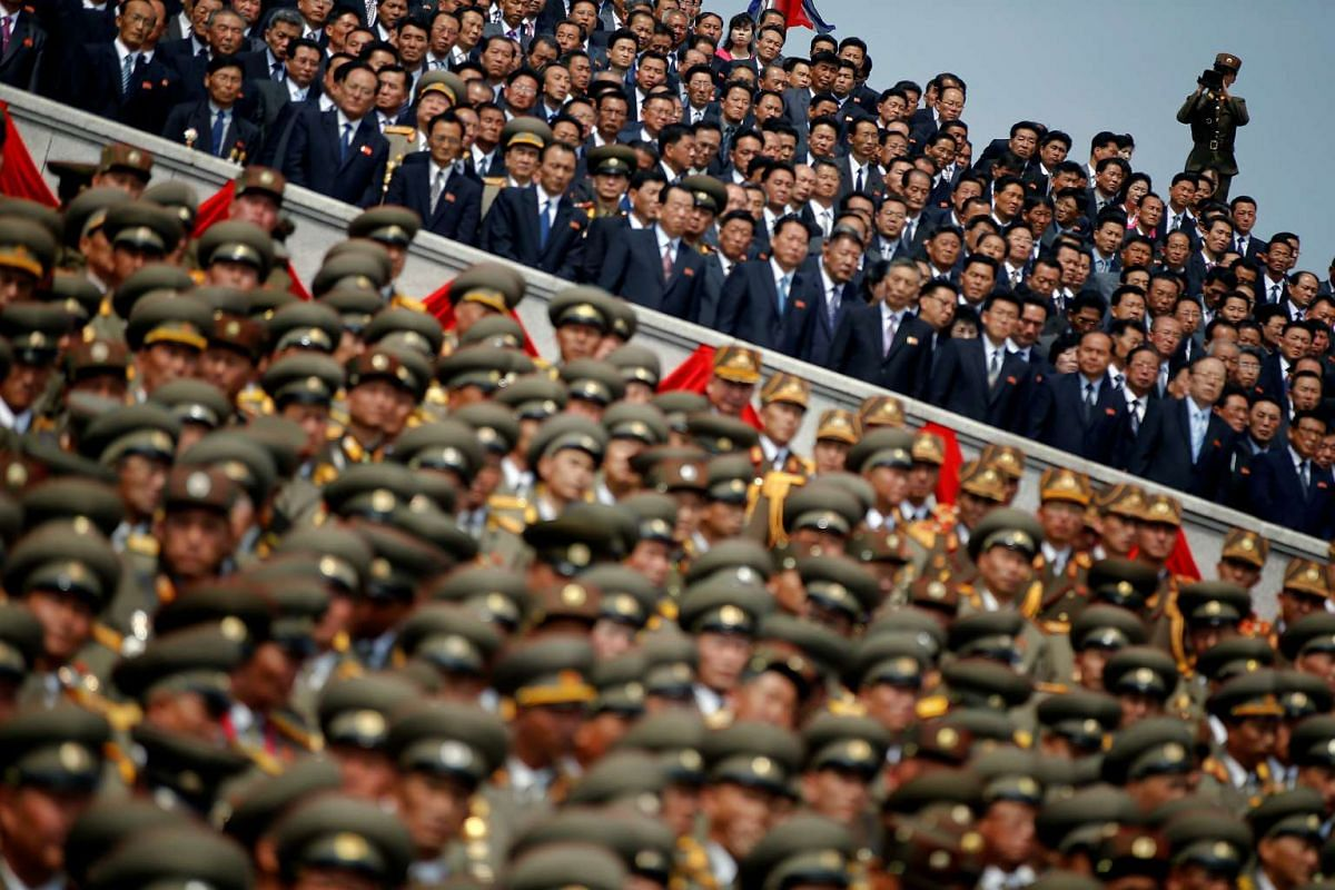 A soldier films North Korean soldiers, officers and high ranking officials attending a military parade marking the 105th birth anniversary of country's founding father in Pyongyang.