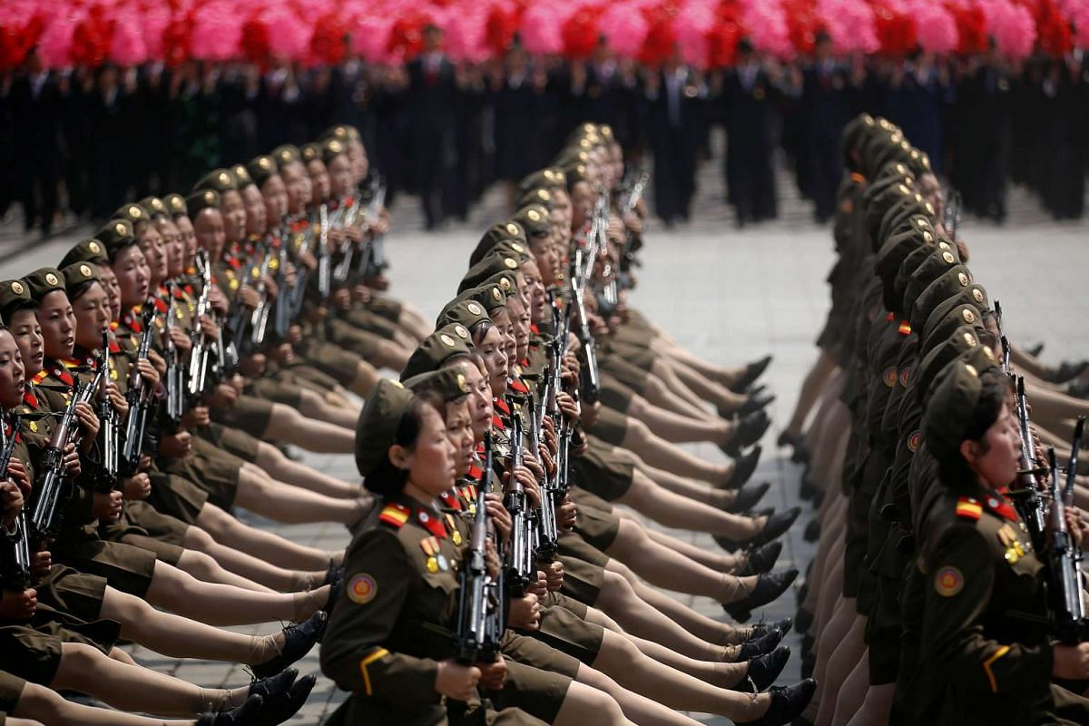 North Korean soldiers march and shout slogans during a military parade marking the 105th birth anniversary of country's founding father in Pyongyang.