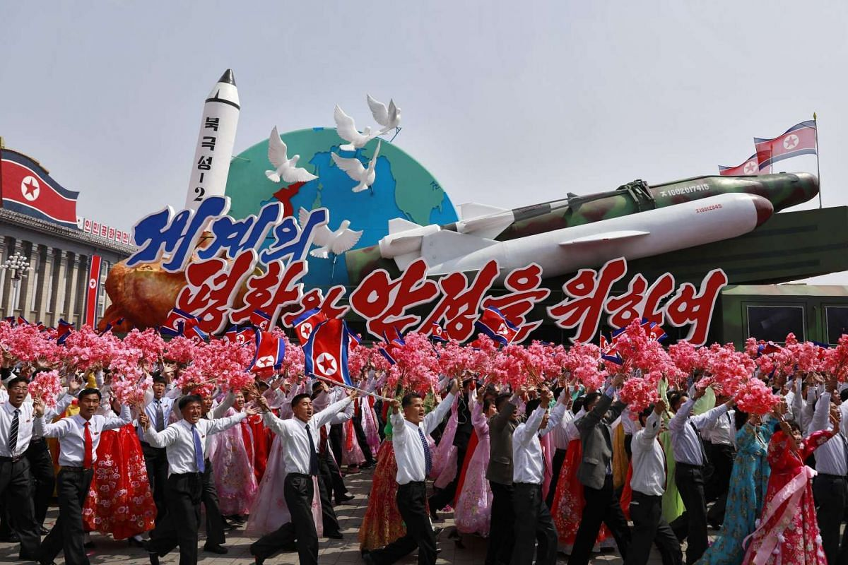 North Korean people waving flowers march with a float carrying replicas of missiles during a parade for the 'Day of the Sun' festival on Kim Il Sung Square in Pyongyang, North Korea, April 15 2017.
