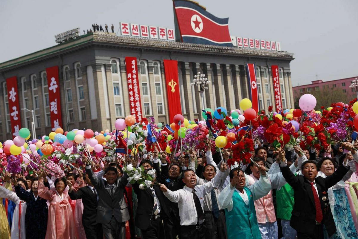 North Korean women and men cheer and wave as they march past during a parade for the 'Day of the Sun' festival on Kim Il Sung Square in Pyongyang, North Korea, April 15 2017.