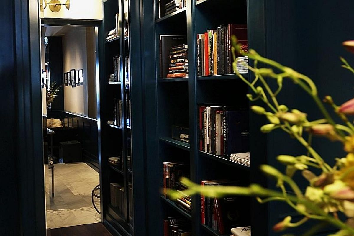 A hidden nook behind a mirrored door is storage for alcohol bottles; the main retail area, which is styled like a living room; and a library (above) with books on cocktails and spirits.