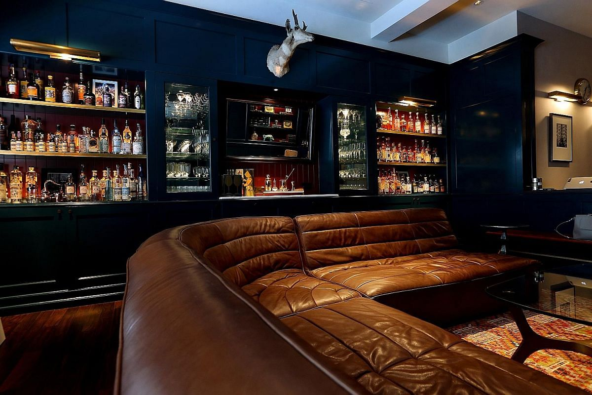 A hidden nook behind a mirrored door is storage for alcohol bottles; the main retail area (above), which is styled like a living room; and a library with books on cocktails and spirits.