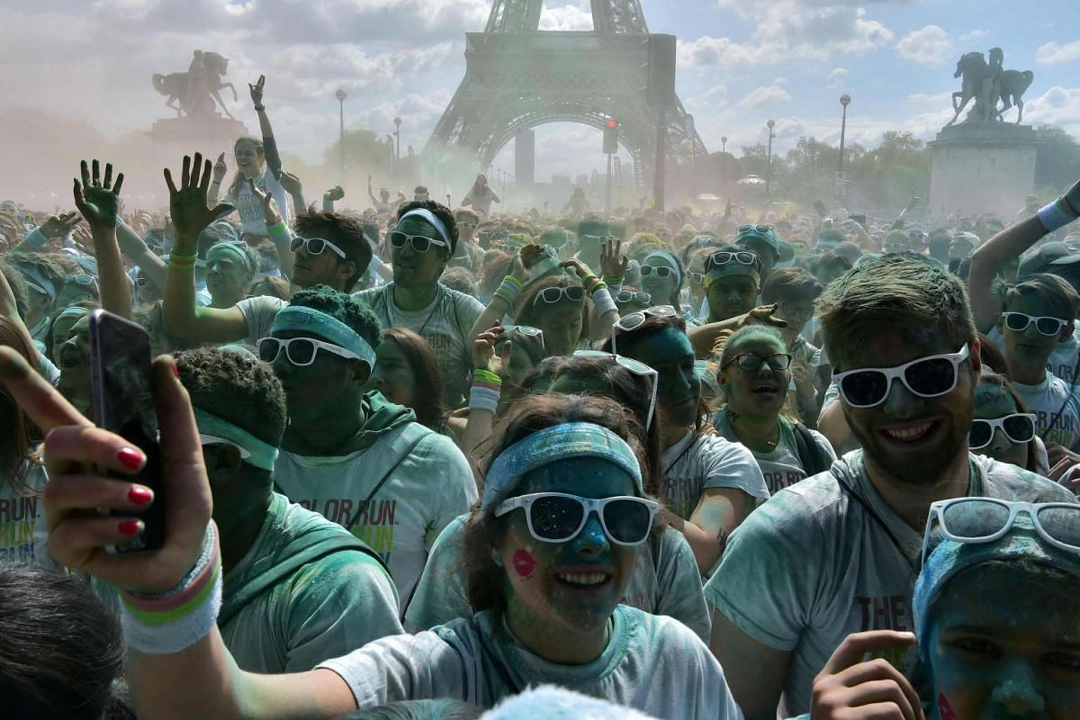 People dance in front of the Eiffel Tower as they take part in the Color Run 2017 's edition, in Paris, on April 16, 2017. PHOTO: AFP