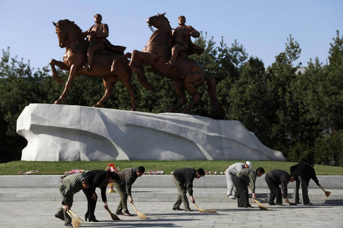 North Korean workers sweep the floor in front of the statues of former Supreme leader Kim Il Sung and Kim Jong Il at Mansudae Art Gallery in Pyongyang, North Korea, on April 12, 2017.