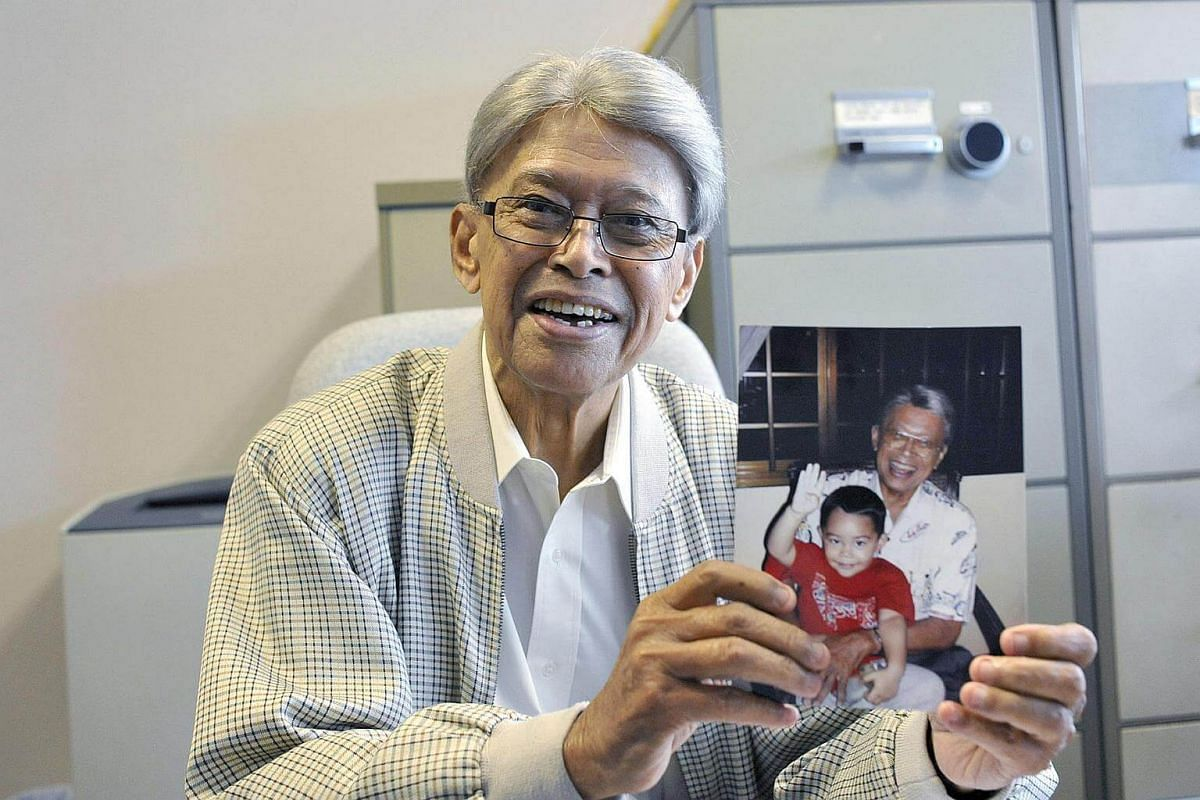 """Mr Othman Wok, holding a 2010 photo of himself and one of his great-grandsons, Daniel, at his Beach Road office, in 2012.  During the interview with My Paper, he said: """"I didn't want to be a politician, I wanted to be a journalist."""""""