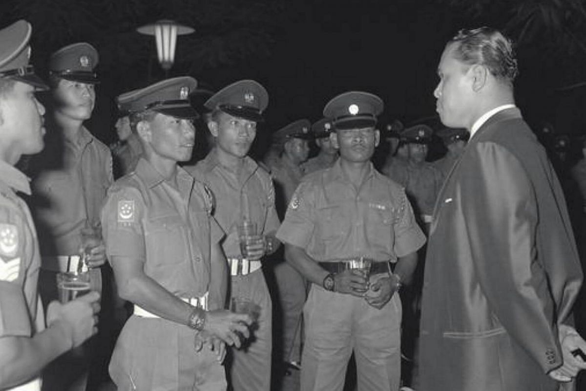 Mr Othman Wok speaking to some of the representatives of the Singapore Infantry Regiment, who had successfully wiped out a band of Indonesian infiltrators at Kota Tinggi during the military confrontation against Malaysia, during a reception at the Is