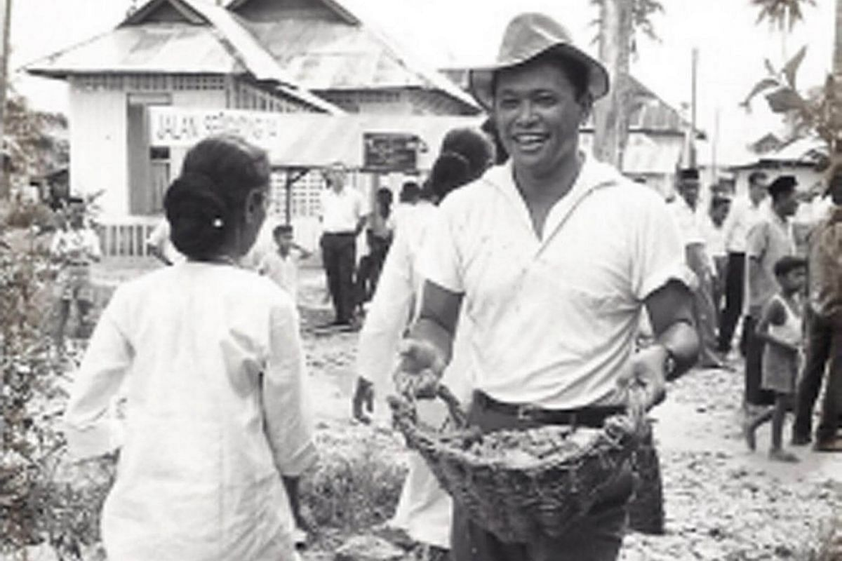 Mr Othman Wok, carrying out gotong royong, or community activities, with residents of Kampong Mat Jambul, Pasir Panjang constituency, in 1966. He served as a People's Action Party (PAP) member of parliament (MP) for the constituency.