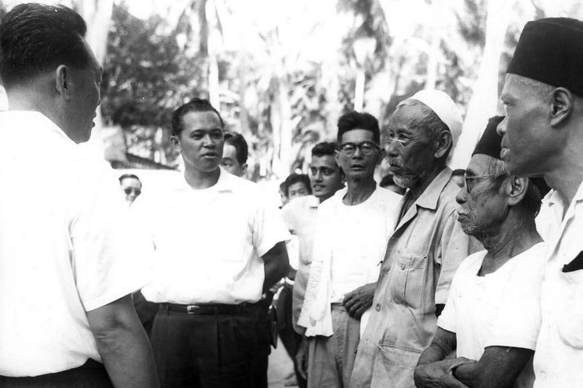 Mr Lee Kuan Yew (left) and Othman Wok (second from left) meeting the constituents of the Old Tampines during their walkabout in the 1960s.