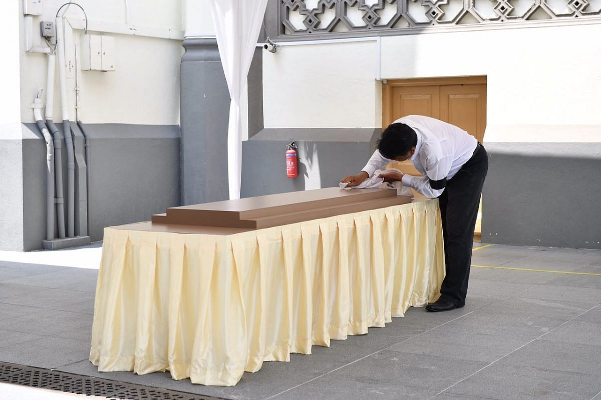 A personnel cleaning the place where the State Flag will be draped over the casket on Tuesday afternoon in Sultan Mosque.
