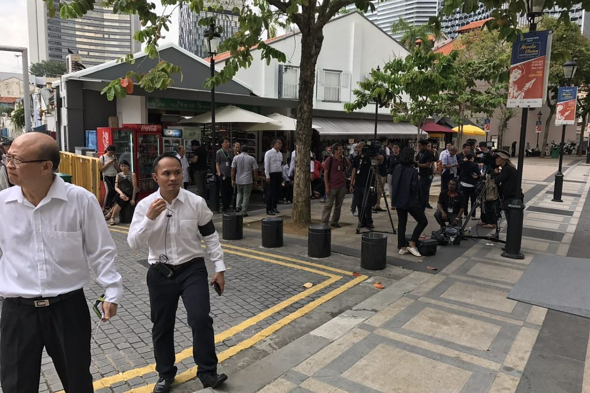 Members of the media and security personnel outside the Sultan Mosque.