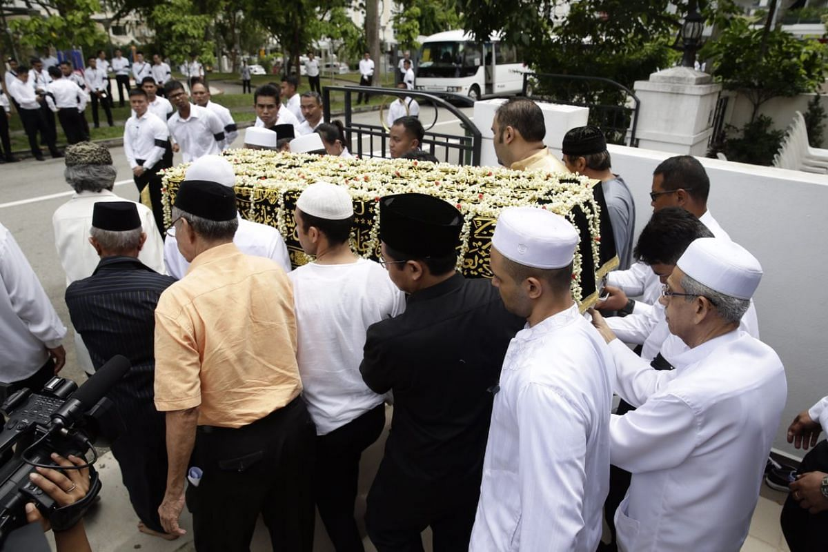Family members and friends carrying Mr Othman Wok's casket.
