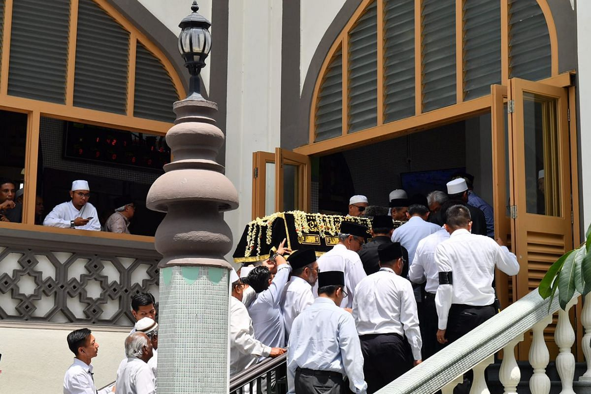 Family members and friends carrying the casket into Sultan Mosque.