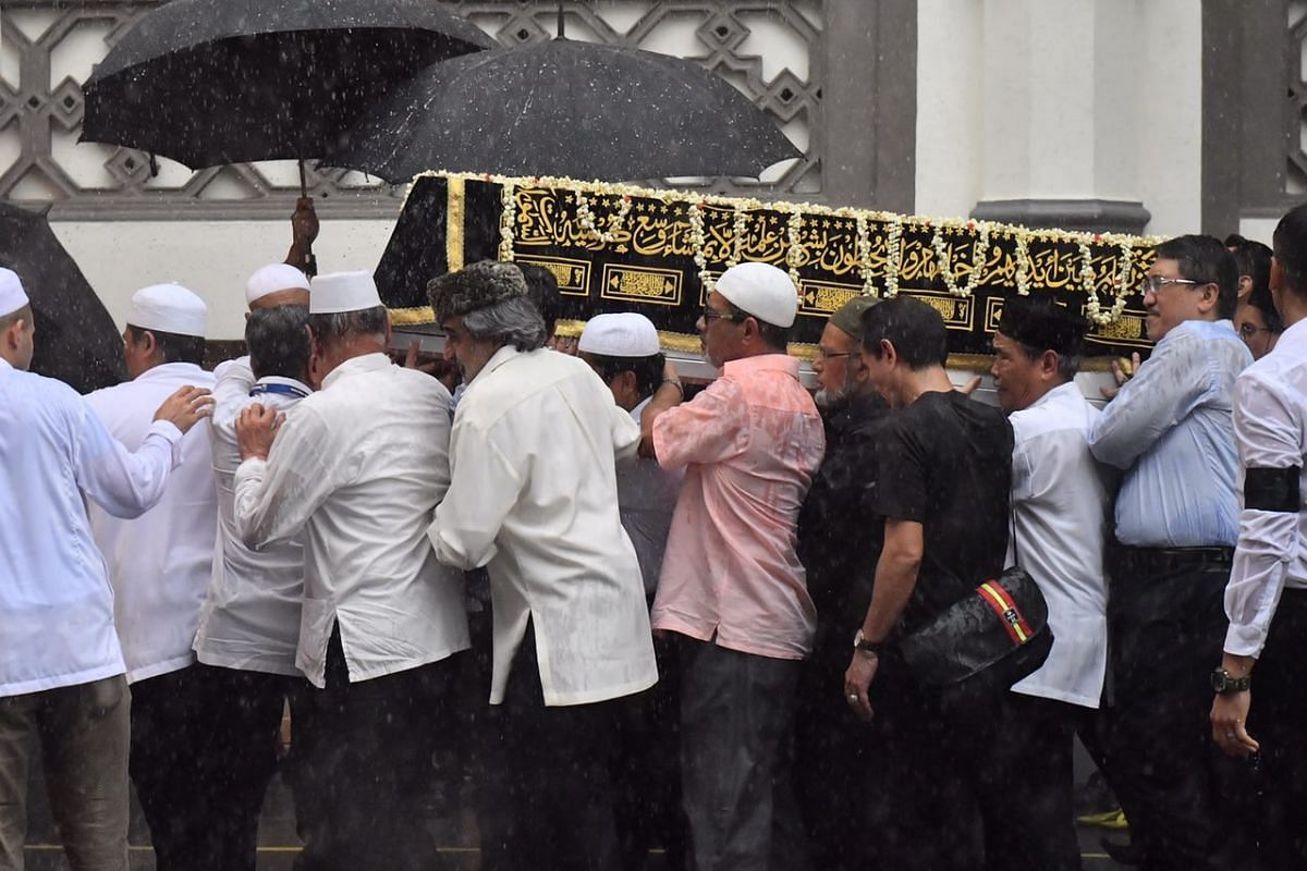 The casket of the late Mr Othman Wok being carried out of the mosque.