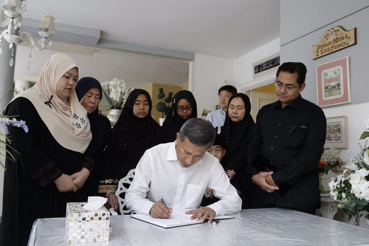 Dr Vivian Balakrishnan signing the condolence book for Mr Othman Wok.