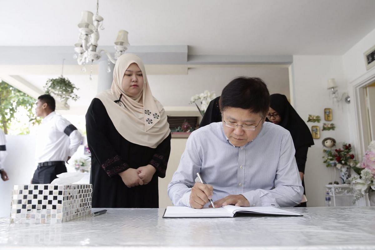 Mr Gan Thiam Poh signing the condolence book.