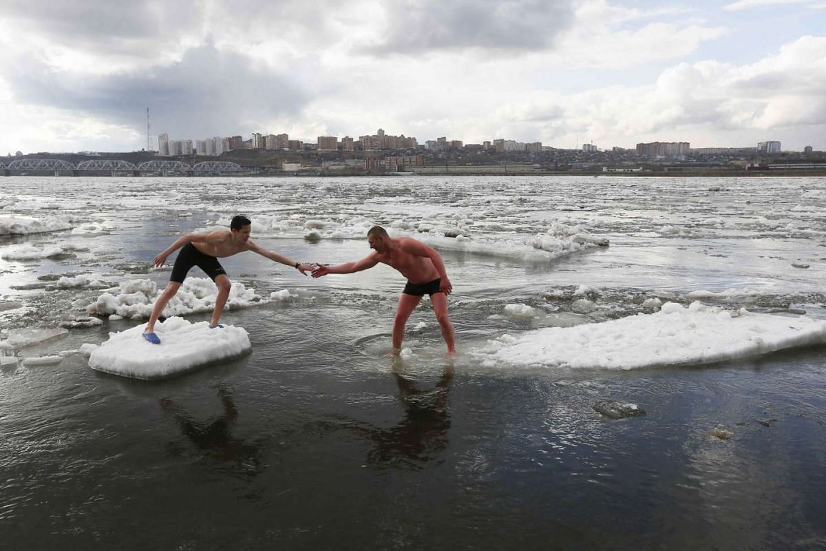 """Members of the """"Yenisei walruses"""" winter swimming club, Alexander Alexandrov (R) and Konstantin Kindinov step from one floe to another during an ice drift on the Yenisei River in Krasnoyarsk, Russia, April 18, 2017. PHOTO: REUTERS"""
