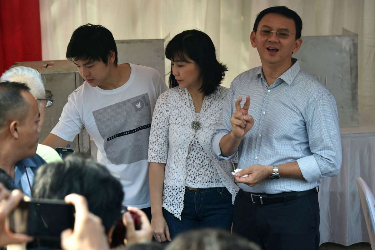 Incumbent Jakarta governor Basuki Tjahaja Purnama (far right) with his wife Veronica and son Nicholas after voting at a polling station.