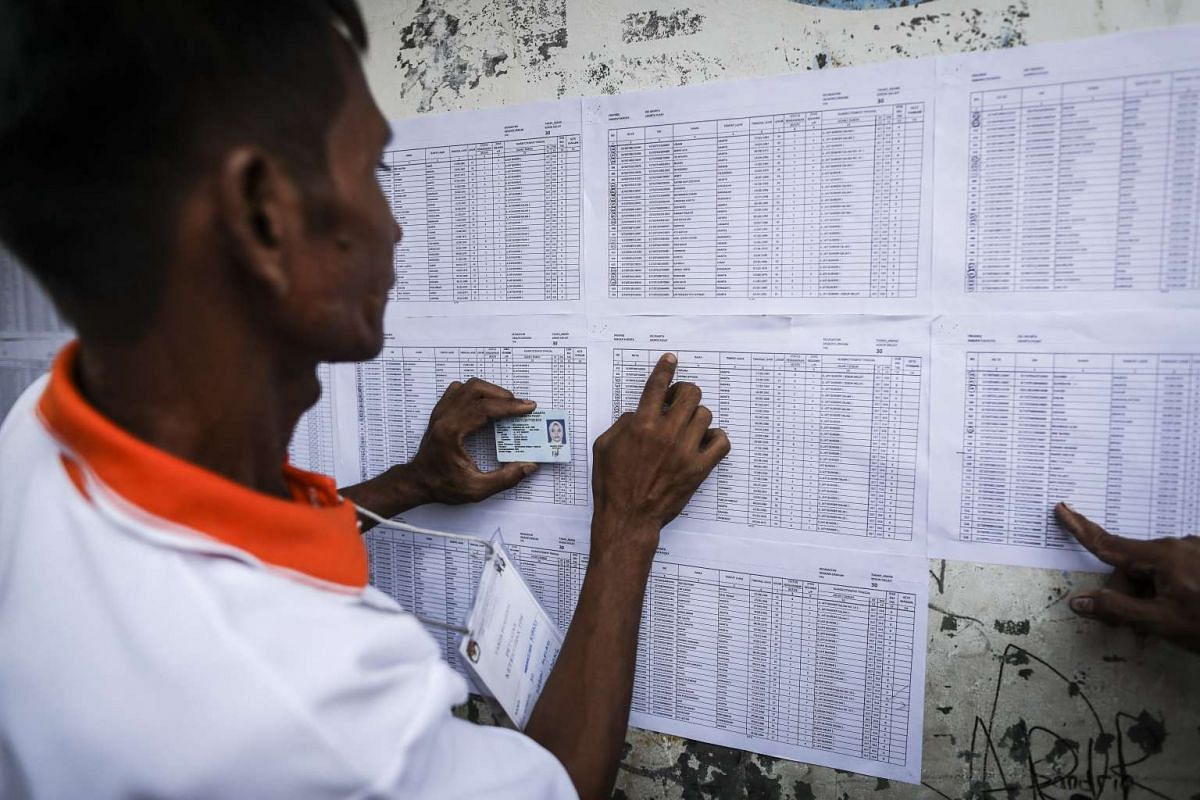 An election official checks the name of a resident on the voters list.