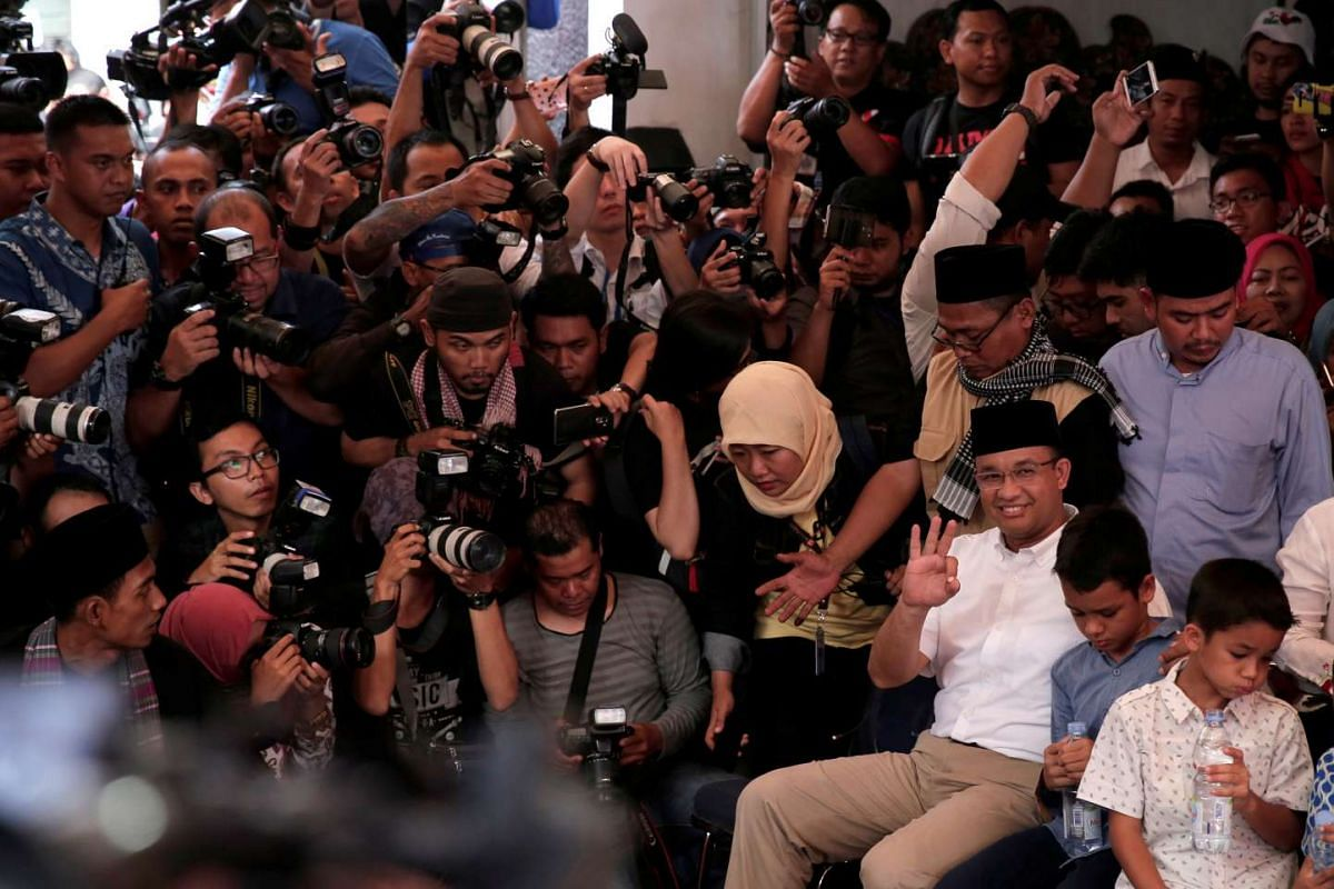 Candidate Anies Baswedan (in white shirt and spectacles) sits down with the media before casting his vote in South Jakarta.