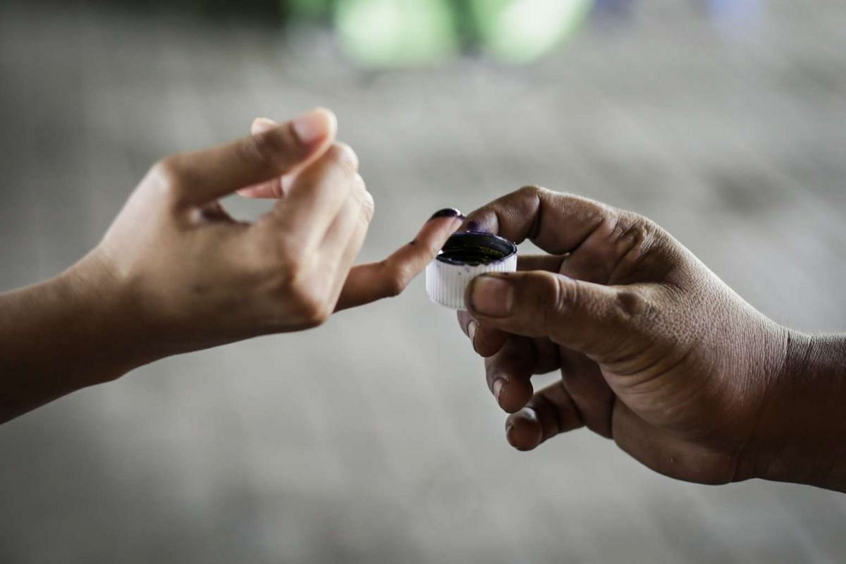 A woman has her finger marked at a polling station to show that she has cast her vote.