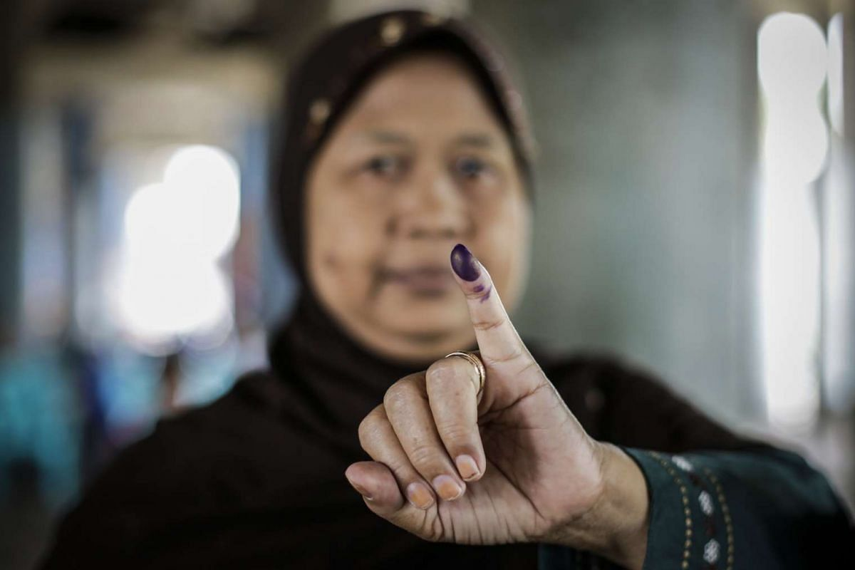 A woman shows her marked finger after casting her vote at a polling station.