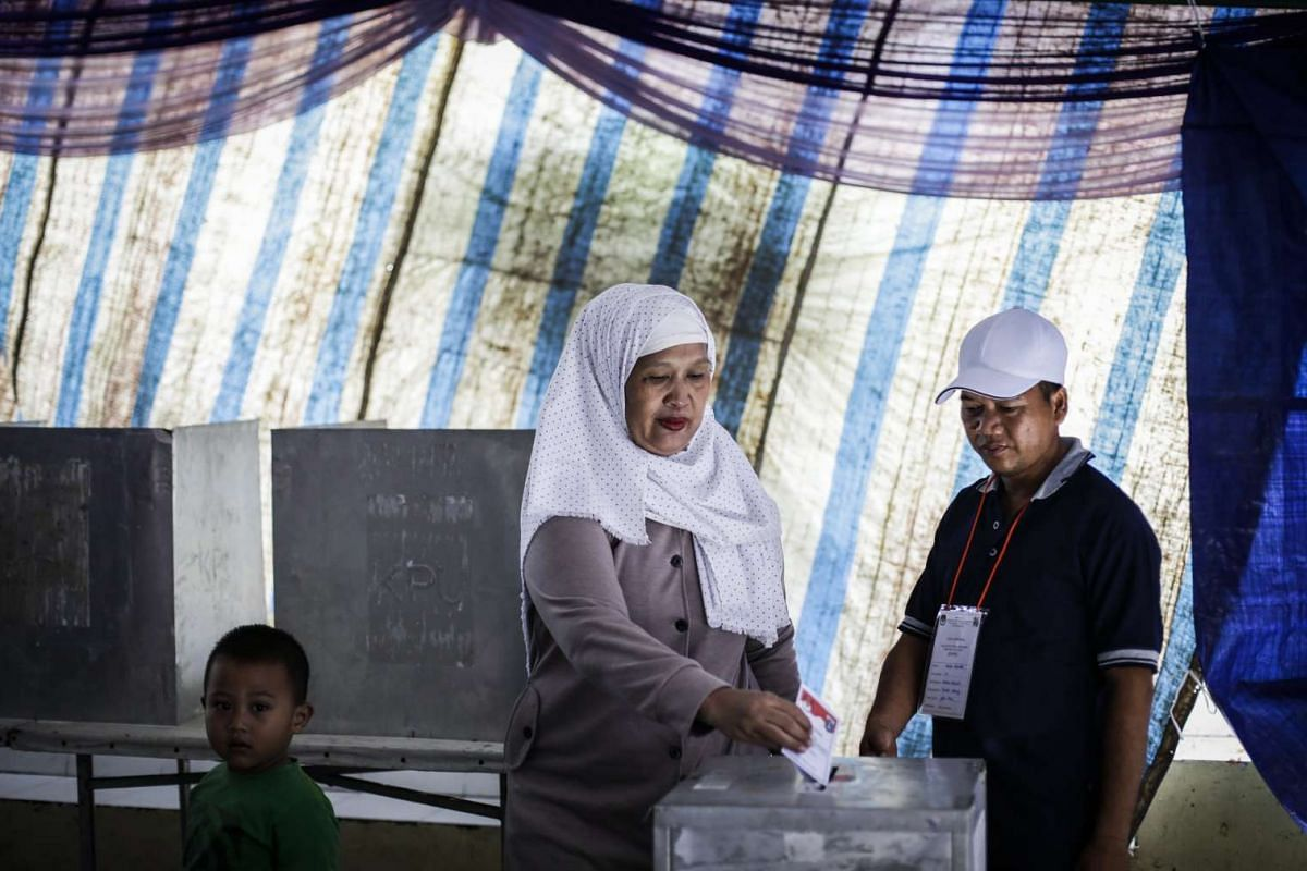 A woman casts her vote at a polling station in Jakarta.
