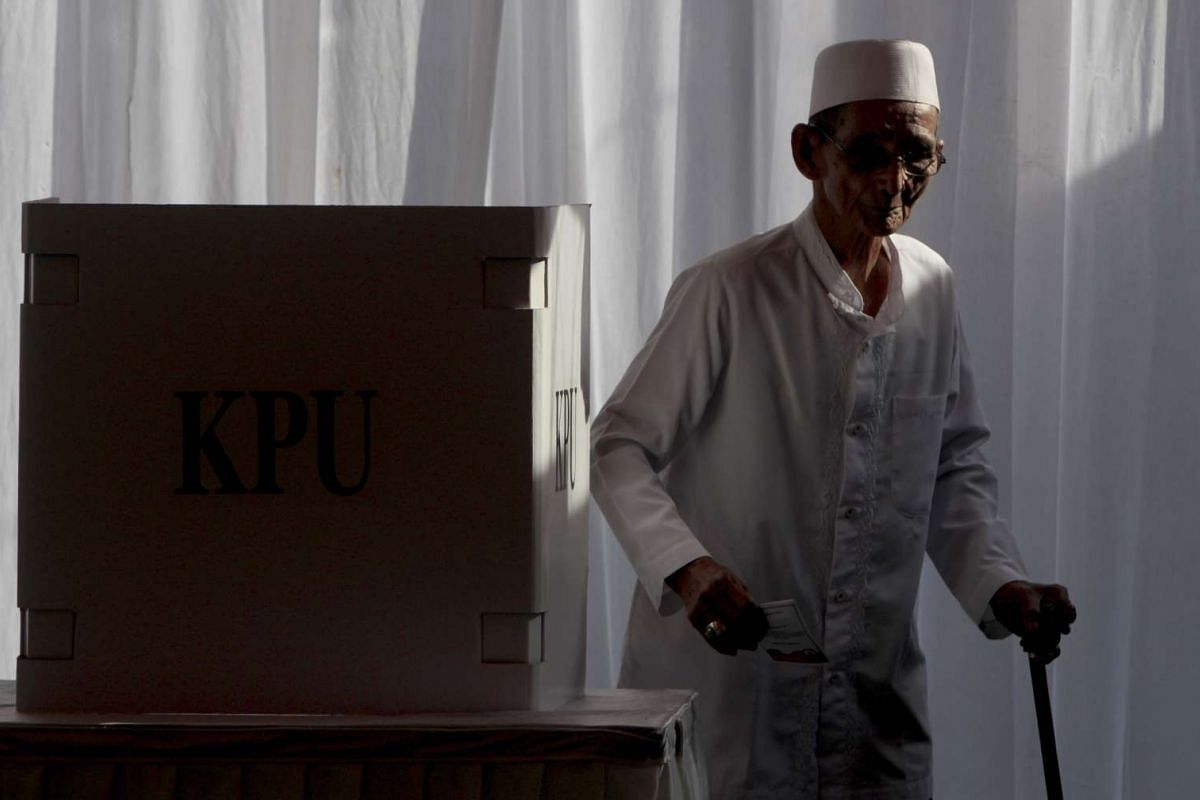 A man holds his ballot paper after voting.