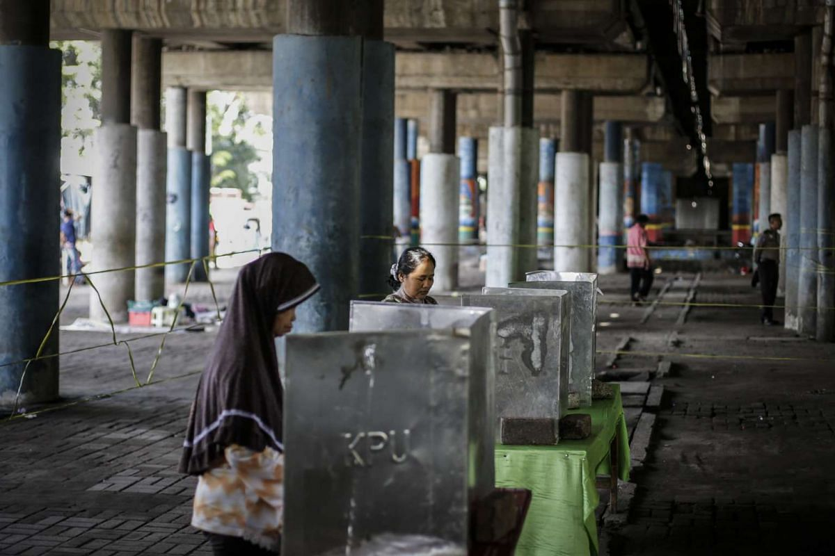 Residents cast their votes at a polling station under a highway bridge in Jakarta.
