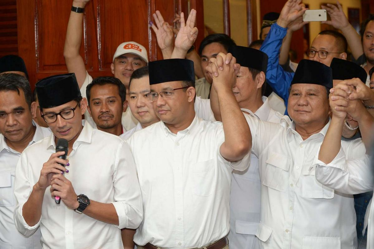 Anis Baswedan (centre), with his deputy Sandiaga Una (left) and Prabowo Subianto (right) of the Gerindra party, hold hands during a press conference.